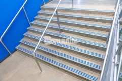 """Several sets of steps throughout Grain Valley High School feature the Bomanite Modena SL Custom Polishing System and the addition of the three-line nose detail engraved into the concrete and filled with """"Grain Valley Blue"""" epoxy creates a unique design element that proudly displays the school's colors."""