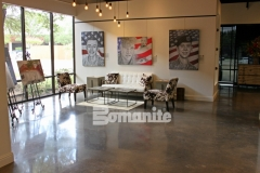 Bomanite Patene Teres custom polished concrete was installed here with Black Orchid concrete dye to add a rustic warmth to the flooring surface in this gallery space and the finished product is a perfect backdrop for the stunning portraiture that was created to commemorate American Fallen Soldiers.