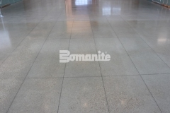 This elegant, high-polish salt and pepper decorative concrete finish was created using the Bomanite VitraFlor Custom Polishing System, adding an unexpected yet beautiful feature inside the Cypress Waters Business Complex.
