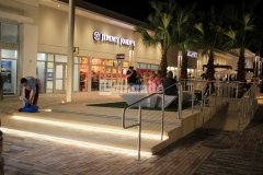 Bomanite Alloy with seashell exposed aggregate was used to create this decorative concrete step plaza and handicap ramp, leading to a distinct and durable finish that complements the beach-industrial aesthetic styling at the Tanger Outlets in Daytona Beach, FL.