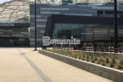 Bomanite Exposed Aggregate Alloy concrete with clear glass aggregates and reflective mirror flakes was incorporated into the Bomanite Sandscape Texture walkways at LAFC Stadium and these contrasting bands serve as line formations that direct fans into the stadium.
