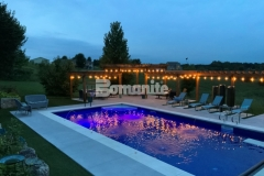 Antique White and Slate Gray Bomanite Revealed were installed here to create decorative concrete pool decking with durability and slip-resistance and the addition of mirror glass and decorative sawcuts enhance the elegant design aesthetic in this backyard retreat.