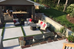 Bomanite Revealed decorative concrete was installed here to create the steps, landing, and this beautiful courtyard area with inlays of grass and planting pockets that help with drainage while adding warmth to the space.