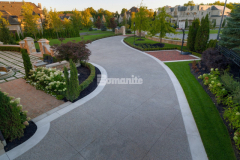 Bomanite Sandscape Texture decorative concrete with Buckskin Integral Color was installed here to create the main driveway and the banding along the driveway was formed and poured separately using a Limestone textured finish, which resulted in a durable and distinct design feature that complements the home's exterior.