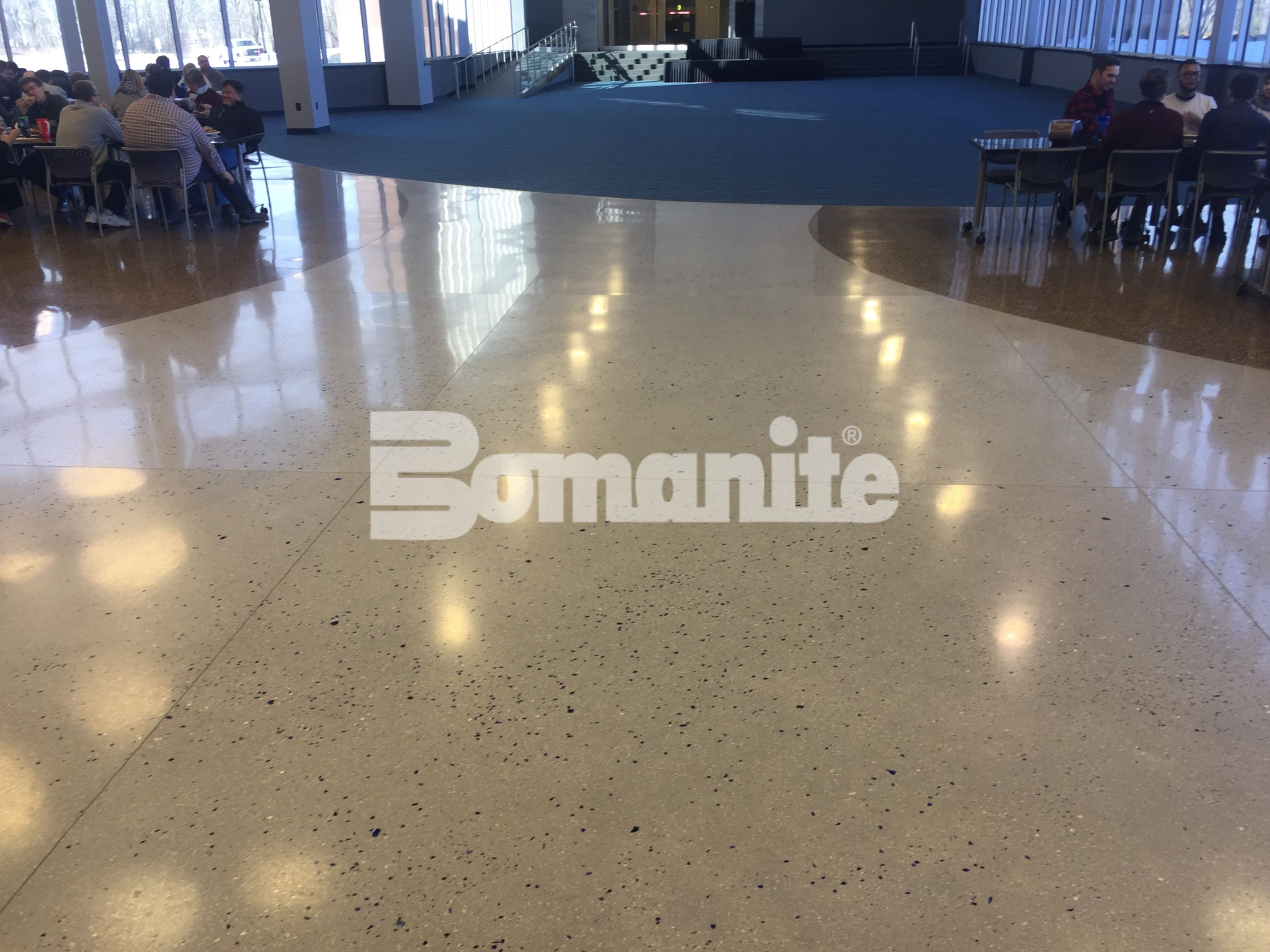 Common Areas at Infinite Campus in Blaine, MN, featuring decorative concrete flooring with Bomanite Custom Polishing Systems using Bomanite Modena Monolithic shimmering and glistening in the sun from the aggregates and glass in the highly polished concrete.
