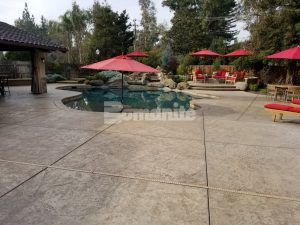 Long view of a decorative concrete pool deck created with Bomanite Imprint Systems using Bomacron Slate Texture located in Fresno, CA, installed by Heritage Bomanite.