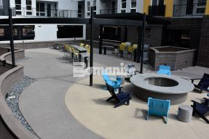Firepit lounge area featuring Bomanite Sandscape Refined Series decorative concrete at CoLab Student Living Housing Community in Denver installed by Colorado Hardscapes using Bomanite Exposed Aggregate Systems, Bomanite Toppings Systems and Board Formed Concrete.